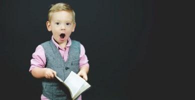 niño con un libro y cara de asombro